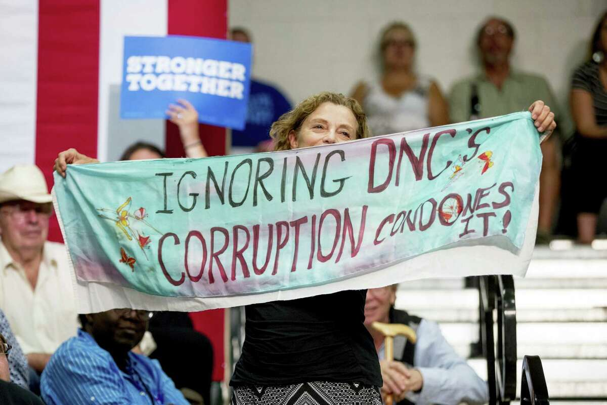 """A woman in the audience holds up a sign that reads """"Ignoring DNC's Corruption Condones It!"""" as Democratic presidential candidate Hillary Clinton speaks Wednesday, Aug. 3, 2016, at a rally at Adams City High School in Commerce City, Colo."""