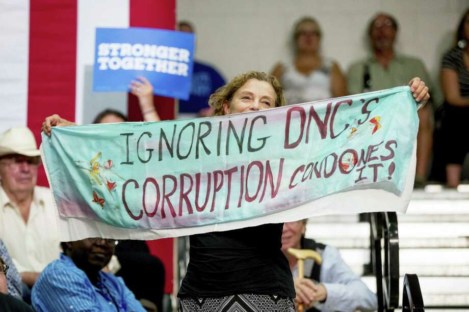 "A woman in the audience holds up a sign that reads ""Ignoring DNC's Corruption Condones It!"" as Democratic presidential candidate Hillary Clinton speaks Wednesday, Aug. 3, 2016, at a rally at Adams City High School in Commerce City, Colo. Photo: AP Photo/Andrew Harnik    / Copyright 2016 The Associated Press. All rights reserved. This material may not be published, broadcast, rewritten or redistribu"