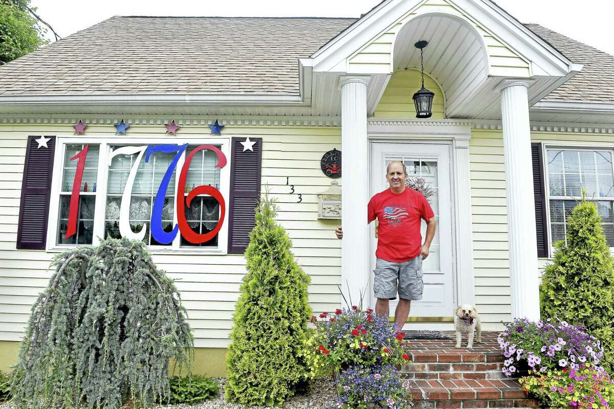 """Bob Barletta in front of his North Have house Friday with """"1776"""" hung over his window. He is continuing a tradition begun by his deceased father, John Barletta, a World War II veteran, who decorated his home with """"1776"""" on the bicentennial of the United States. At right is his dog, Lexi."""