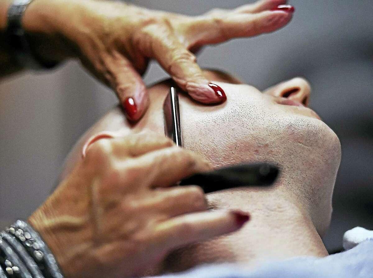 Hushin uses a straight razor on a customer.