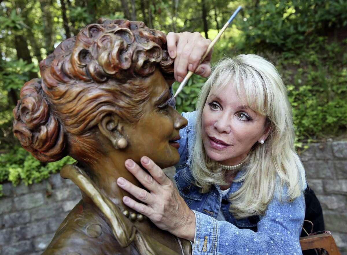 """In this Wednesday, July 20, 2016, photo, artist Carolyn Palmer prepares to apply a cold patina to her bronze statue of Lucille Ball in Saddle River, N.J. The sculptor was chosen to create a replacement statue for one dubbed """"Scary Lucy,"""" in the late actress Ball's hometown. The much-maligned statue of Ball will be replaced after it drew worldwide attention as """"Scary Lucy,"""" according to the mayor of the western New York village where the 1950s sitcom actress and comedian grew up and her life-size bronze has stood since 2009."""