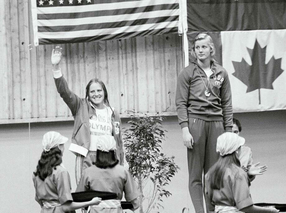 In this 1976 file photo, East German swimmer Kornelia Ender, right, who was awarded the Olympic gold medal for the 200 meter freestyle event, stands on the podium, as her main opponent, silver medalist Shirley Babashoff of the U.S. acknowledges the crowd during the medal ceremony in Montreal. Photo: The Associated Press File Photo   / AP