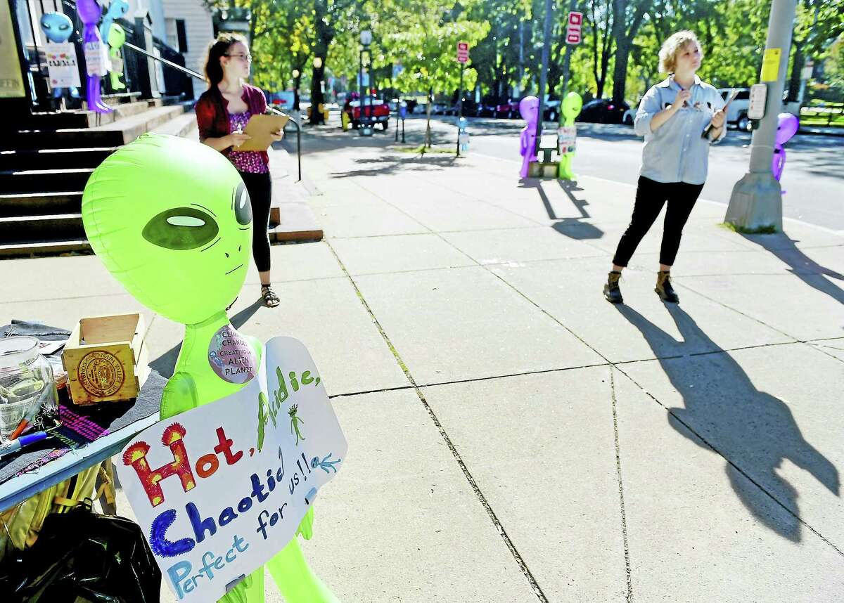 (Peter Hvizdak - New Haven Register)New Haven Leon Sister City Project interns Sarah Beth Watson, left, and Lydia Post, representing the Healthy City / Healty Climate coalition, with inflatable alien caricatures, wait on the corner of College Street and Elm Street in New Haven Thursday morning, October 6, 2016 with a petition and climate change informational handouts launching
