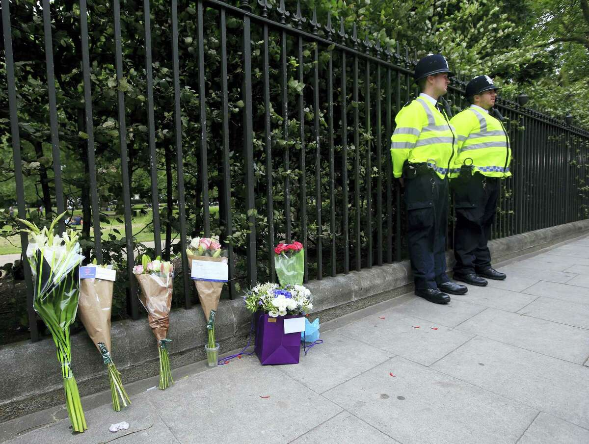 Floral tributes rest against railings Thursday Aug. 4, 2016, near the scene of a fatal stabbing on Wednesday night in Russell Square, London. London police say they have found no signs of radicalization in a knife attack which killed an American woman and injured five other people in London's Russell Square.