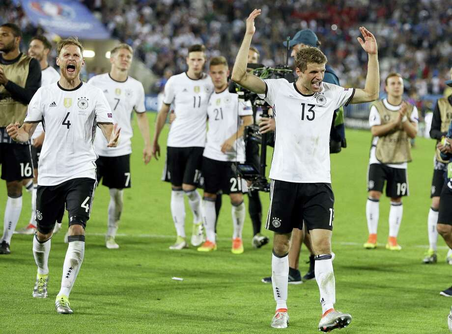 Germany's Thomas Mueller, right, celebrates with teammates after Germany won the penalty shootout against Italy on Saturday. Photo: Thanassis Stavrakis — The Associated Press   / AP