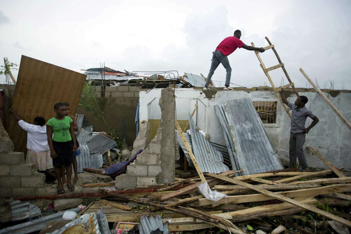 Residents repair their homes destroyed by Hurricane Matthew in Les Cayes, Haiti, Thursday. Two days after the storm rampaged across the country's remote southwestern peninsula, authorities and aid workers still lack a clear picture of what they fear is the country's biggest disaster in years.