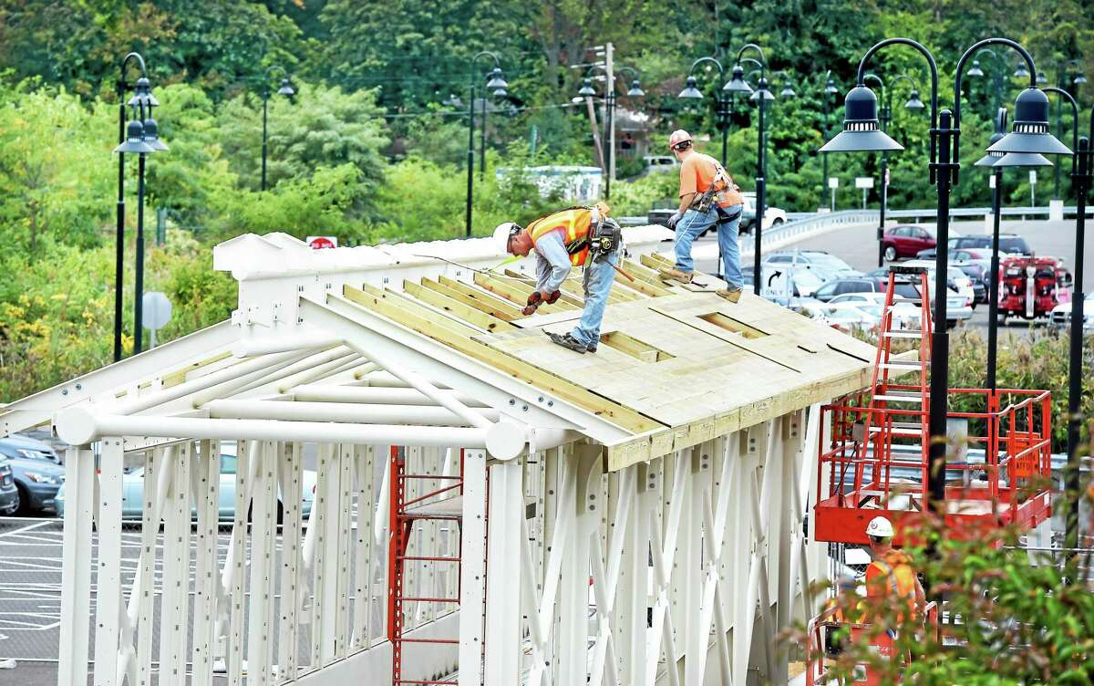 Richard Cyr (center) screws boards into place on the roof of a pedestrian bridge that will cross over the railroad tracks at the Branford Station on Sept. 9, 2014.