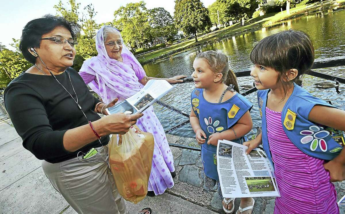 Daisy Scouts Isabelle Phelan, 5, third from left, and Christina Ann Barbara, 6, right, spread the word about the harm in feeding the waterfowl Wednesday to West Haven residents Usha Jadeja, left, and her mother, Mohanba Gohil, at the duck pond in Milford.
