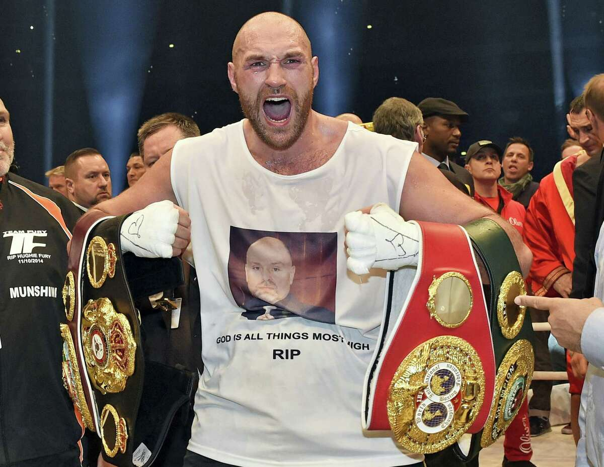 In this Nov. 29, 2015 photo, Britain's new world champion Tyson Fury, celebrates with the WBA, IBF, WBO and IBO belts after winning the world heavyweight title fight against Ukraine's Wladimir Klitschko in Duesseldorf, western Germany. Tyson Fury's boxing career could be over after the reigning IBF, WBO and WBA heavyweight champion announced his retirement in a profanity-filled tweet on Monday Oct. 3, 2016.