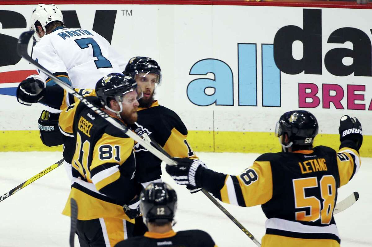 Pittsburgh Penguins' Nick Bonino, center, celebrates his game-winning goal against the San Jose Sharks with Phil Kessel (81) and Kris Letang (58) during the third period in Game 1 of the Stanley Cup final series Monday, May 30, 2016, in Pittsburgh. (AP Photo/Gene J. Puskar)
