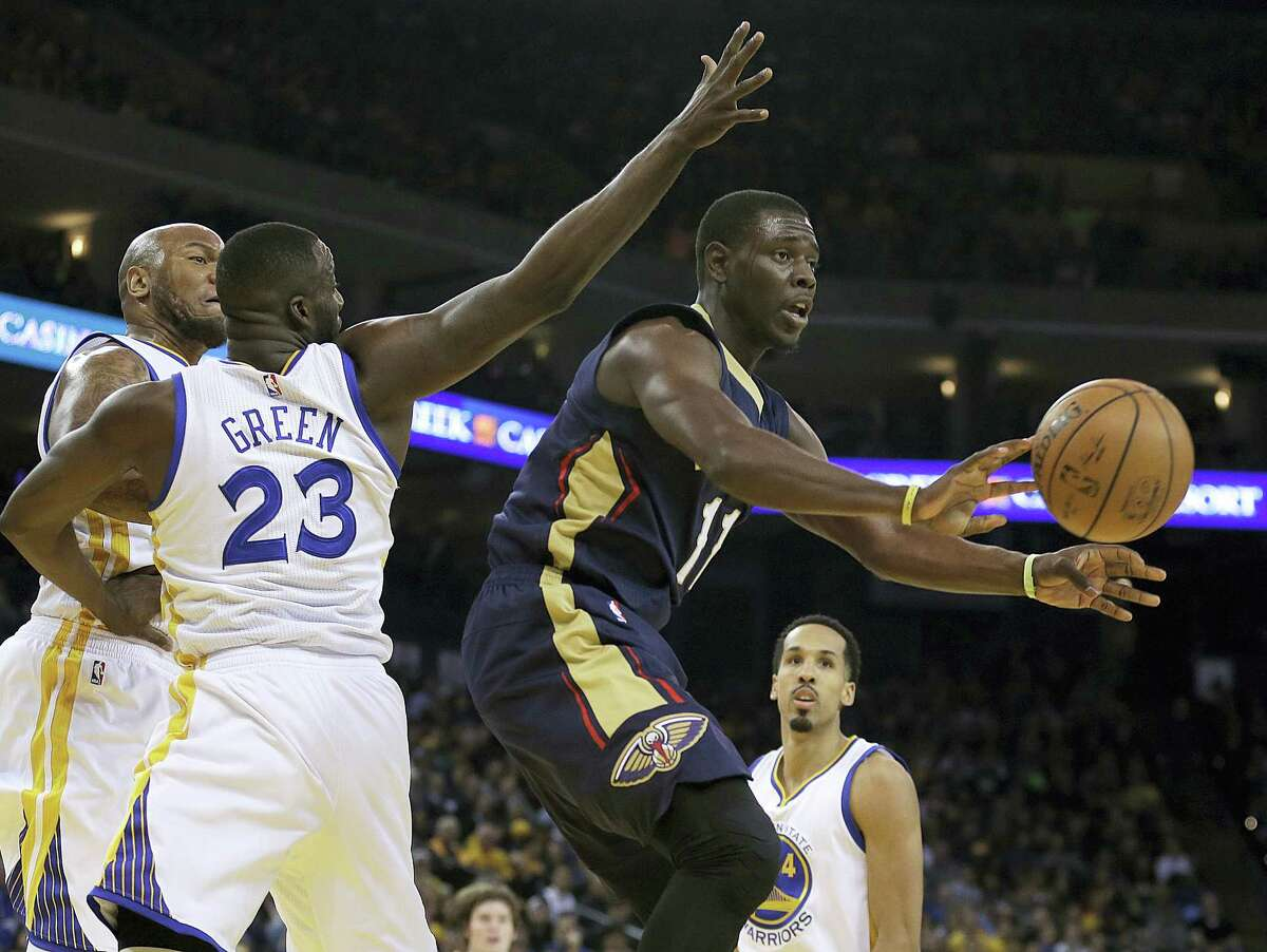 The Pelicans' Jrue Holiday, right, passes away from the Warriors' Draymond Green during a game last season.