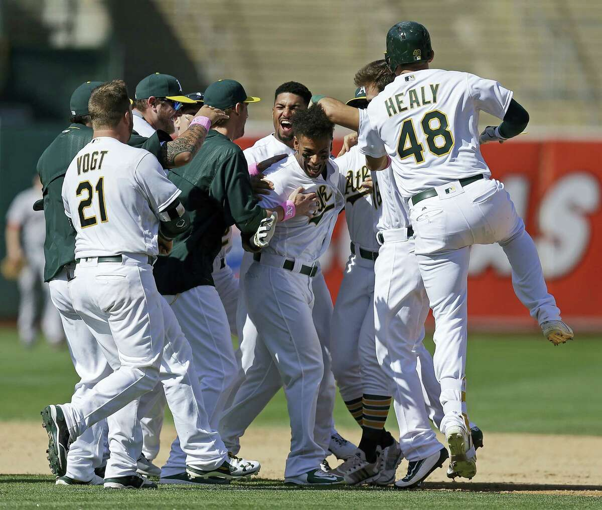 Oakland Athletics' Khris Davis, center, celebrates after making the winning hit against the Boston Red Sox in the ninth inning of a baseball game Sunday, Sept. 4, 2016, in Oakland, Calif. (AP Photo/Ben Margot)