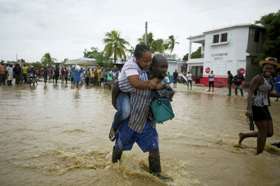 A man piggybacks a woman across a a street flooded by a nearby river overflowing from the heavy rains caused by Hurricane Matthew, in Leogane, Haiti, Wednesday, Oct. 5, 2016. Rescue workers in Haiti struggled to reach cutoff towns and learn the full extent of the death and destruction caused by Matthew as the storm began battering the Bahamas on Wednesday and triggered large-scale evacuations along the U.S. East Coast. ( AP Photo/Dieu Nalio Chery) Photo: AP / Copyright 2016 The Associated Press. All rights reserved.