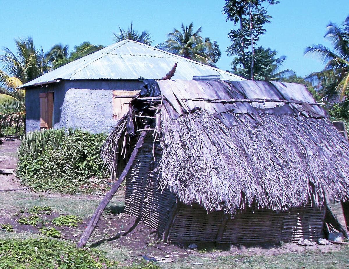 "COURTESY HAITIAN HEALTH FOUNDATION A ""happy house"" built by the Haitian Health Foundation sits behind a typical Haitian home."