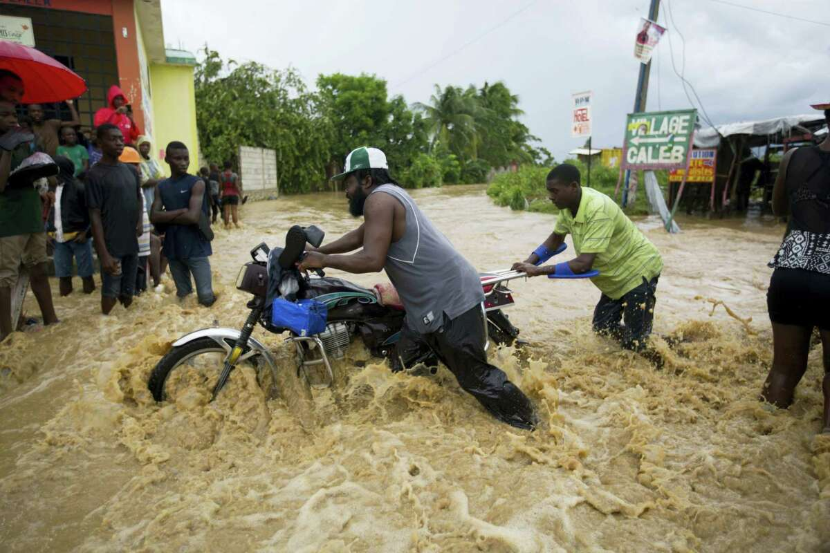 Two men push a motorbike through a street flooded by a nearby river that overflowed from heavy rains caused by Hurricane Matthew, in Leogane, Haiti, Wednesday.