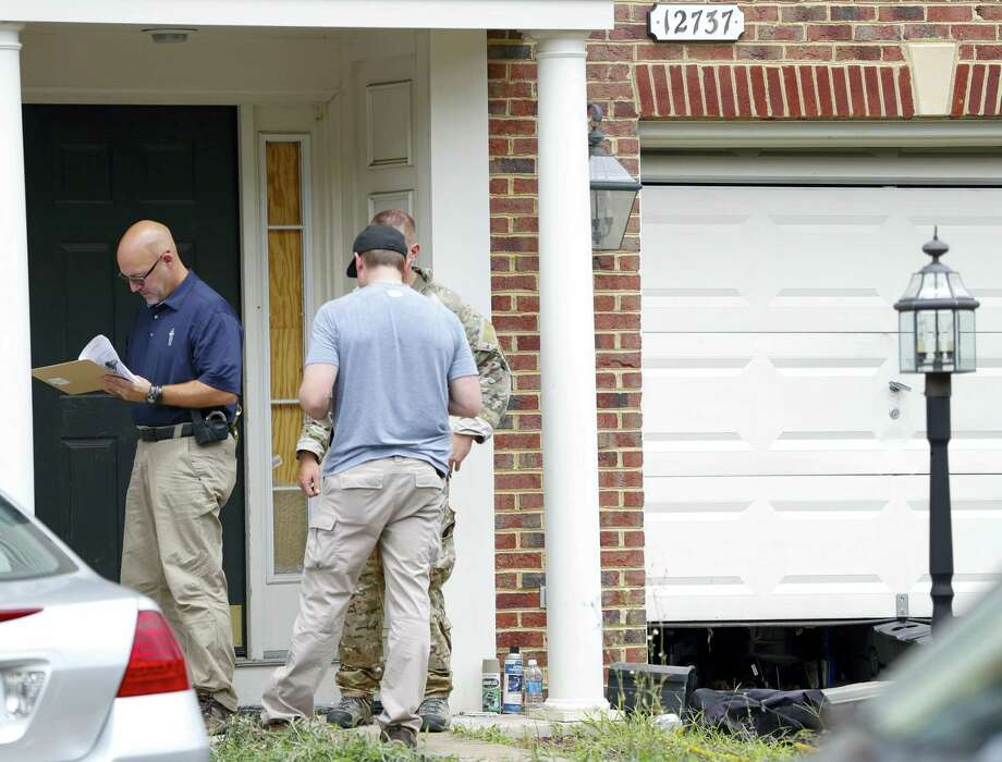 Law enforcement officers stand outside the home of Nicholas Young, a Washington Metro Transit Officer on Wednesday in Fairfax, Va. Young was arrested at Metro's headquarters in Washington and charged with a single count of attempting to provided material support to a terrorist group. Photo: AP Photo — Pablo Martinez Monsivais / Copyright 2016 The Associated Press. All rights reserved. This material may not be published, broadcast, rewritten or redistribu