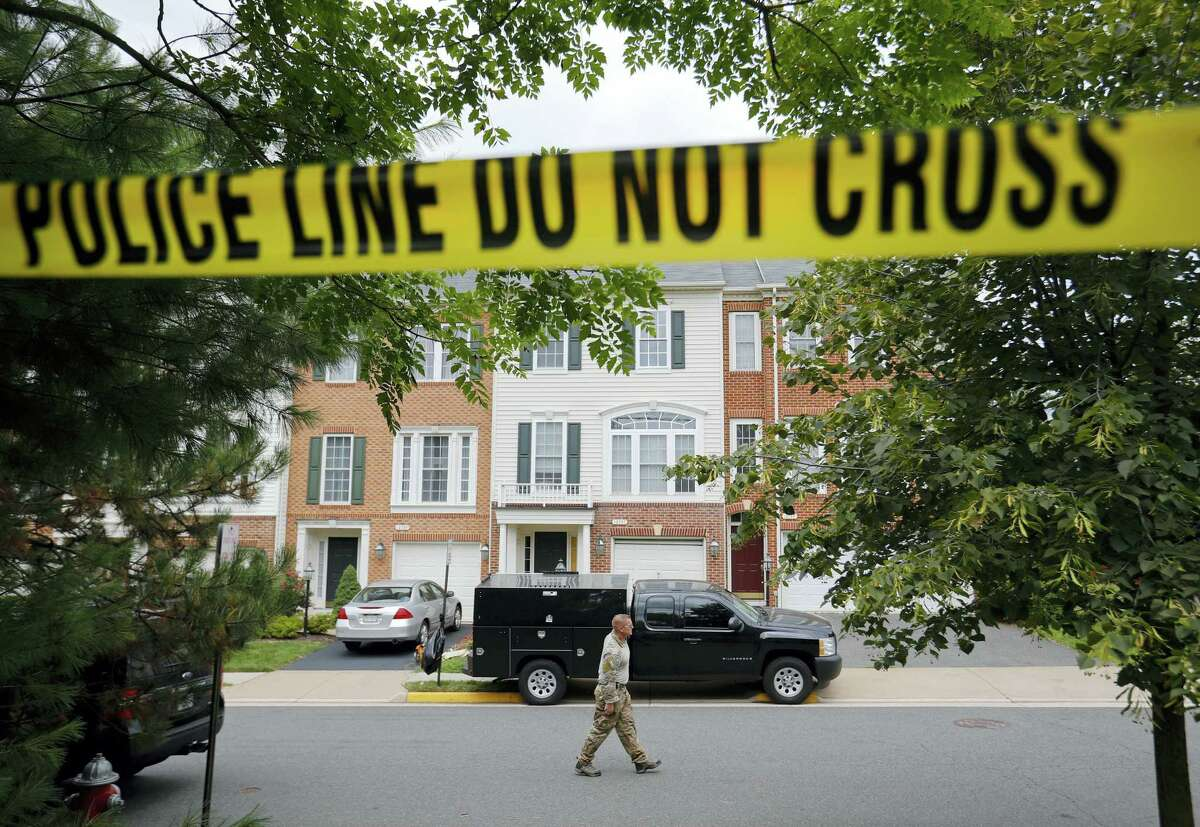 A law enforcement officer walks on the street outside the home of Nicholas Young, a Washington Metro Transit Officer on Wednesday in Fairfax, Va. Young was arrested at Metro's headquarters in Washington and charged with a single count of attempting to provided material support to a terrorist group.