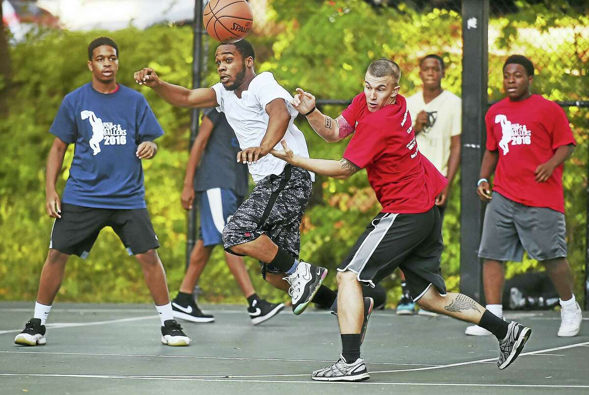 """Warren Ligon, second from left, in white, and Officer Marco Correa, third from left, battle for a rebound at the """"Cops and Ballers"""" community basketball tournament Wednesday at Edgewood Park in New Haven."""