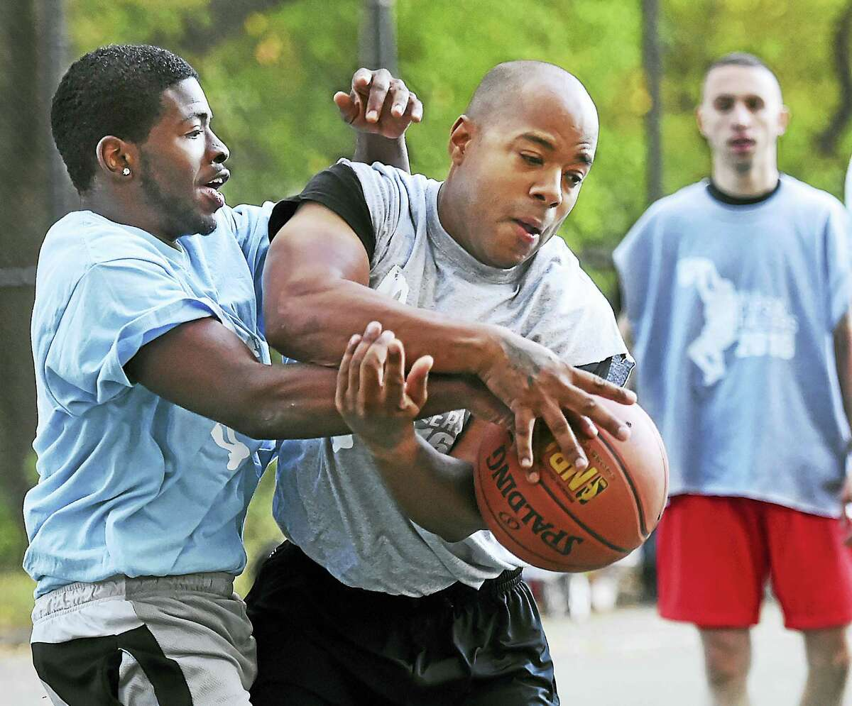 """Trevon Gray, left, and Officer John Moore battle for posession as Officer Greg Ammon keeps his eye on the play at the """"Cops and Ballers"""" community basketball tournament Wednesday in New Haven."""