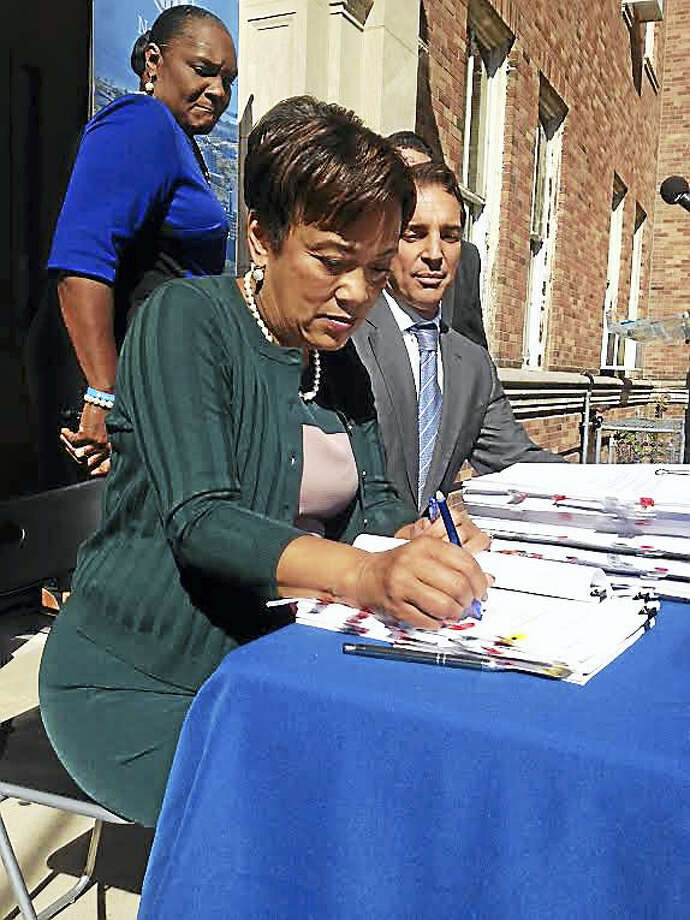 Mayor Toni Harp signs development agreement with Randy Salvatore of RMS Companies. They are in front of the Welch Annex School, which will be converted to housing. Serena Neal-Sanjurjo, head of the Livable City Initiative, is behind them. Photo: MARY O'LEARY — NEW HAVEN REGISTER