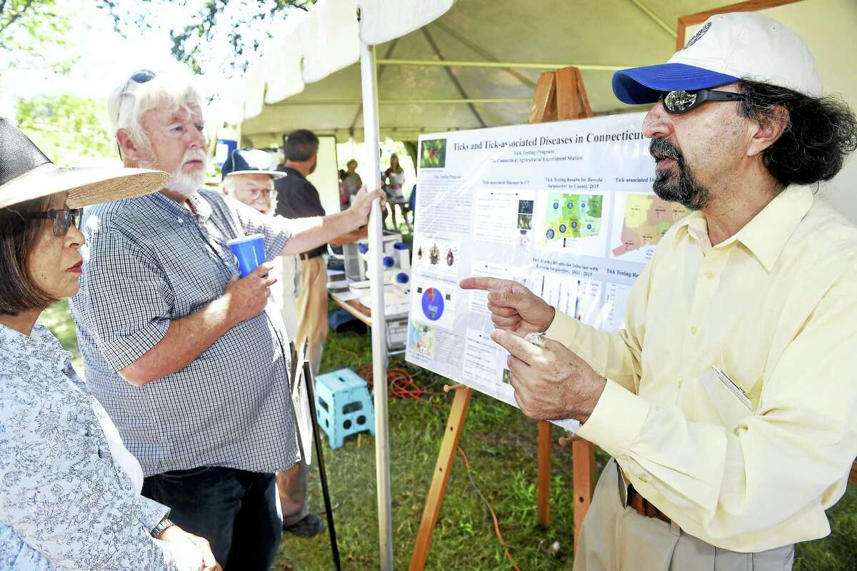 Left to right, Sachiyo Furuka-wa of Weston and Donald Charbonneau of Bethany listen to Dr. Goudarz Molaei of the Connecticut Agricultural Experiment Station talk about ticks during Plant Science Day at Lockwood Farm in Hamden Monday.