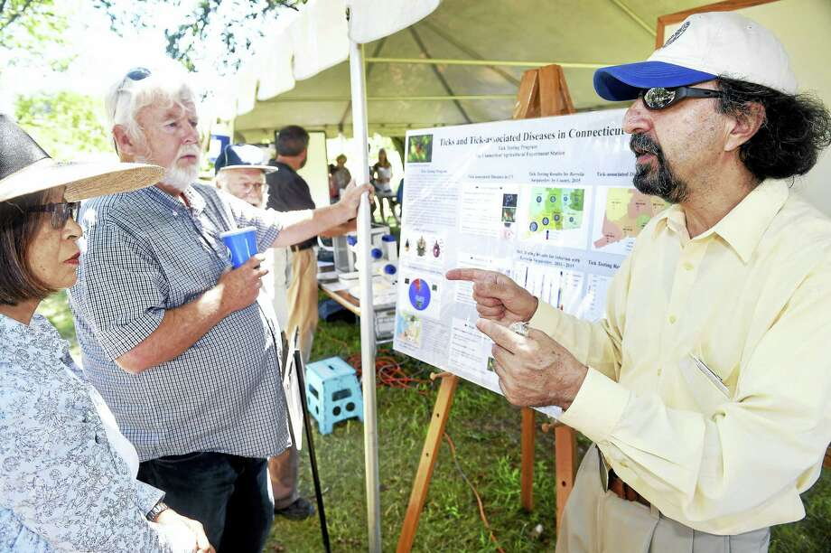Left to right, Sachiyo Furuka-wa of Weston and Donald Charbonneau of Bethany listen to Dr. Goudarz Molaei of the Connecticut Agricultural Experiment Station talk about ticks during Plant Science Day at Lockwood Farm in Hamden Monday. Photo: Arnold Gold — New Haven Register