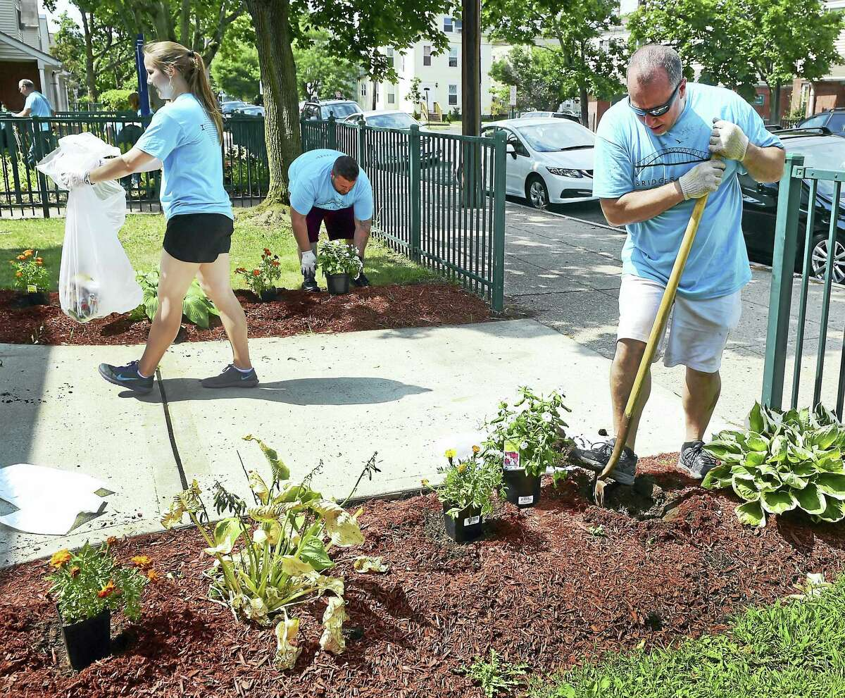 Holly Stewart of Hamden and the City Church of New Haven, left, and Vinny Celentano and John Zurco of the 180 Center Ministry on Grand Avenue in New Haven, participated in flower planting and yard cleanup at the Waverly Townhouses in New Haven Saturday.
