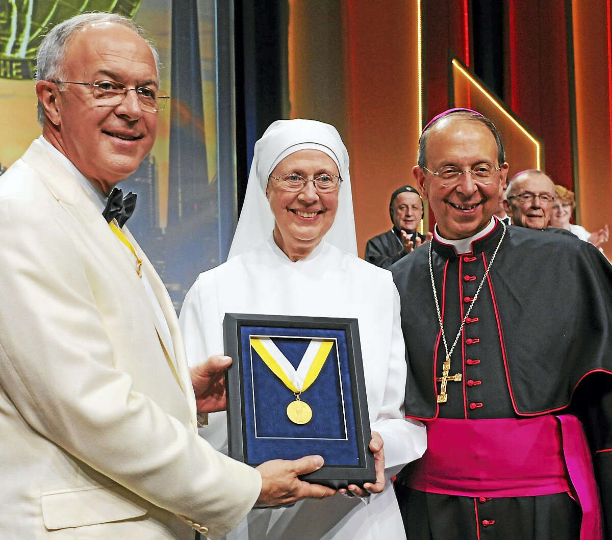 Supreme Knight Carl A. Anderson, left, presents the Knights of Columbus' Gaudium et Spes Award to Mother Loraine Marie Maguire, superior of the Baltimore Province of the Little Sisters of the Poor. At right is Archbishop William Lori of Baltimore.
