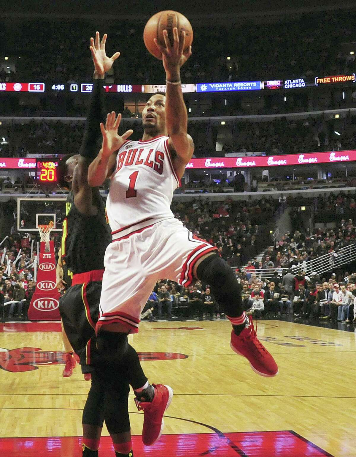 In this March 28, 2016 photo, former Chicago Bulls guard Derrick Rose (1) goes to the basket on Atlanta Hawks guard Jeff Teague during the first half of an NBA basketball game in Chicago.
