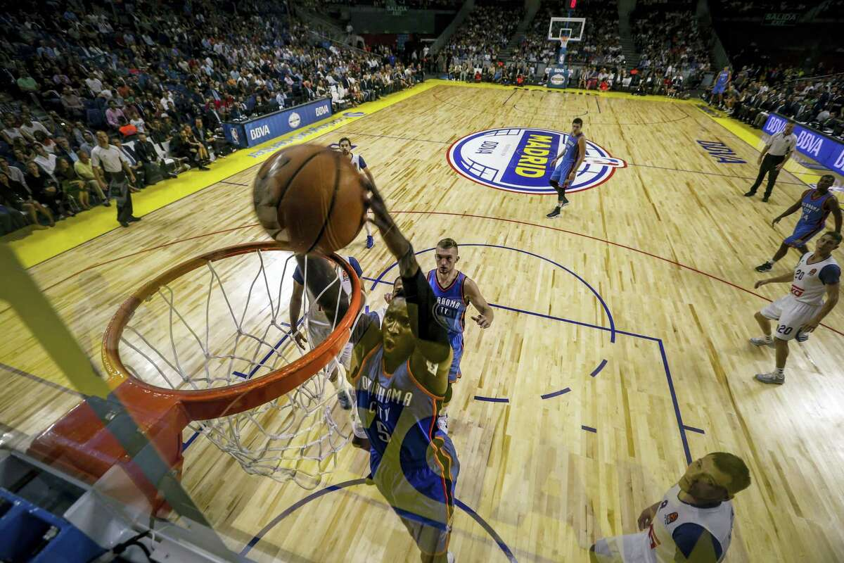 Oklahoma City Thunder guard Victor Oladipo swings on the basket after dunking during a NBA Global Games basketball match between Real Madrid and Oklahoma City Thunder in Madrid on Oct. 3, 2016.