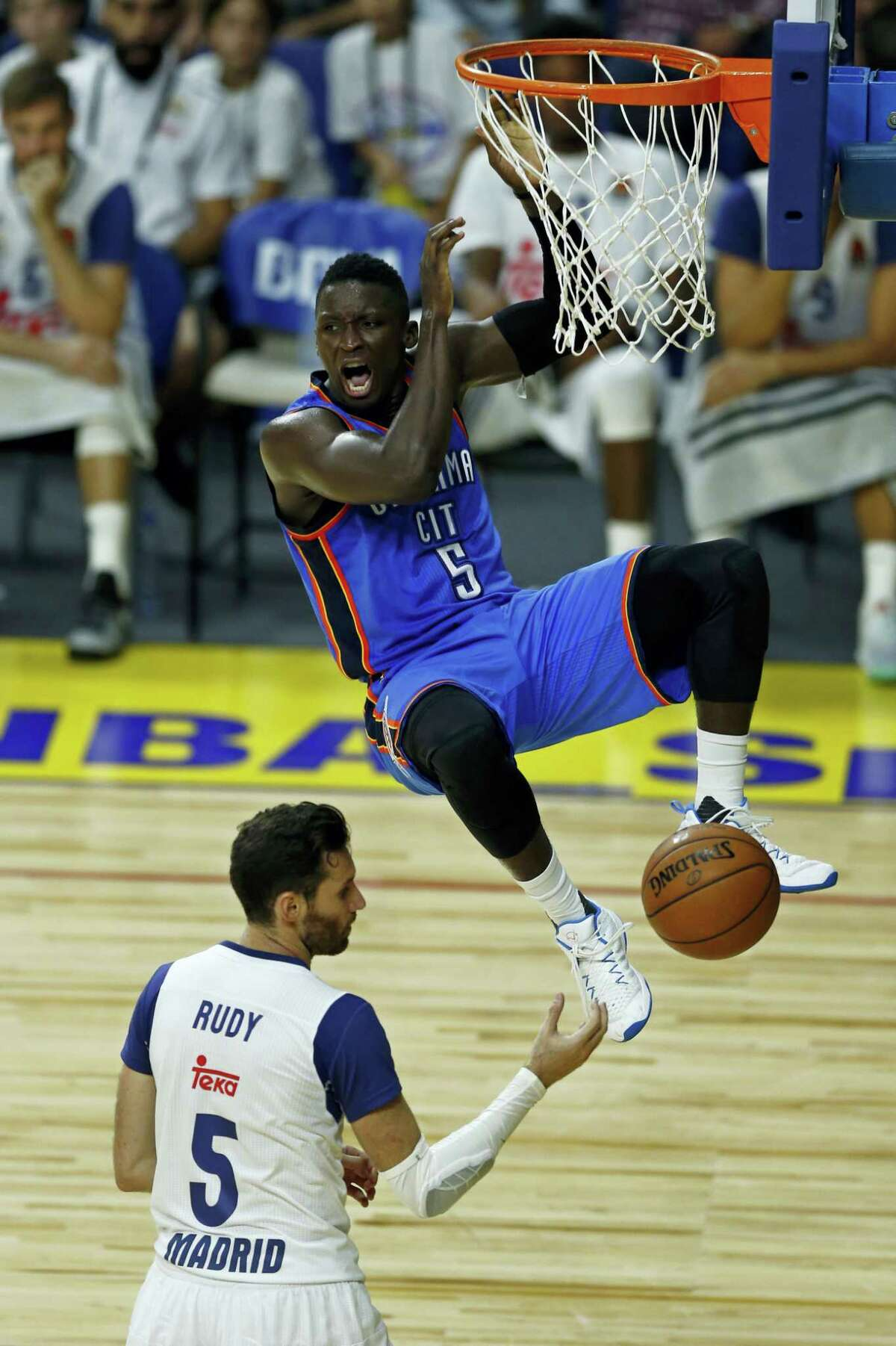 Oklahoma City Thunder guard Victor Oladipo swings on the basket after dunking during a NBA Global Games basketball match between Real Madrid and Oklahoma City Thunder in Madrid, Spain on Oct. 3, 2016.