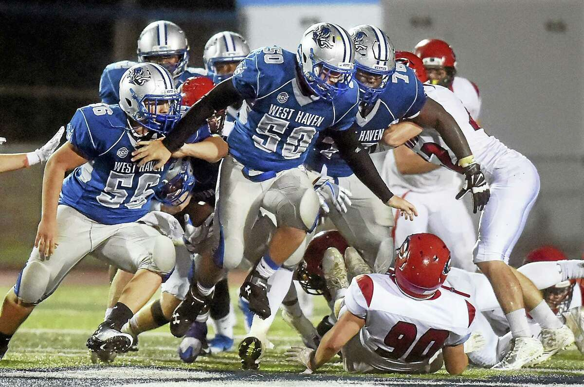Bobby Hawkins (50) leads a charge of West Haven players, including Jimmy Lanziero (56) and Byron Dickens (76) in a 41-14 victory over Cheshire, Friday, September 30, 2016, at Ken Strong Stadium in West Haven.