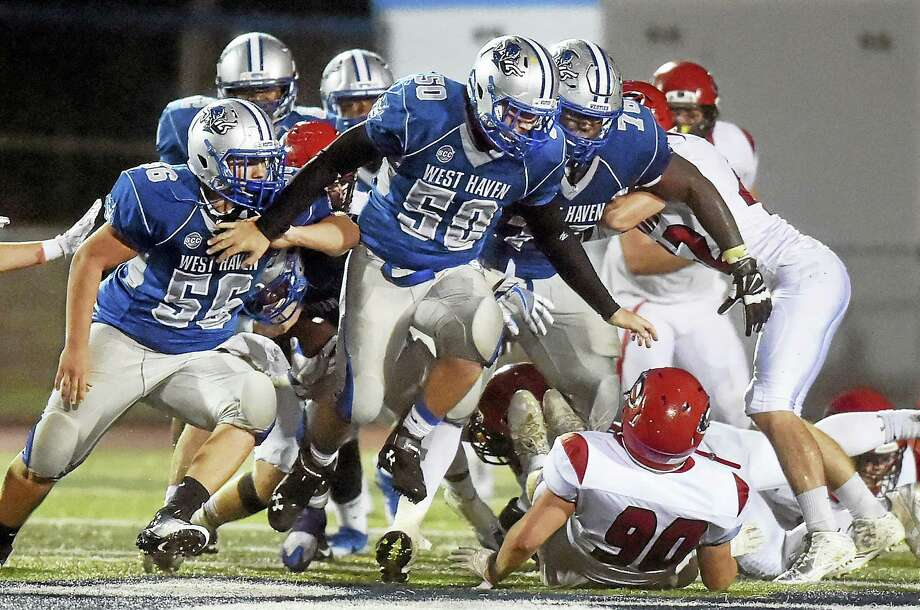 Bobby Hawkins (50) leads a charge of West Haven players, including Jimmy Lanziero (56) and Byron Dickens (76) in a 41-14 victory over Cheshire, Friday, September 30, 2016, at Ken Strong Stadium in West Haven. Photo: Catherine Avalone — New Haven Register   / New Haven RegisterThe Middletown Press