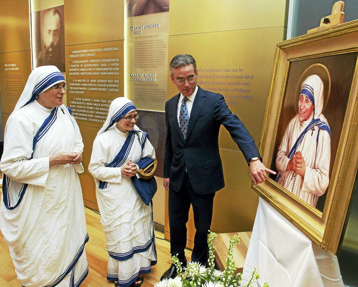 Artist Chas Fagan shows his portrait of Mother Teresa to two members of her order, the Missionaries of Charity.