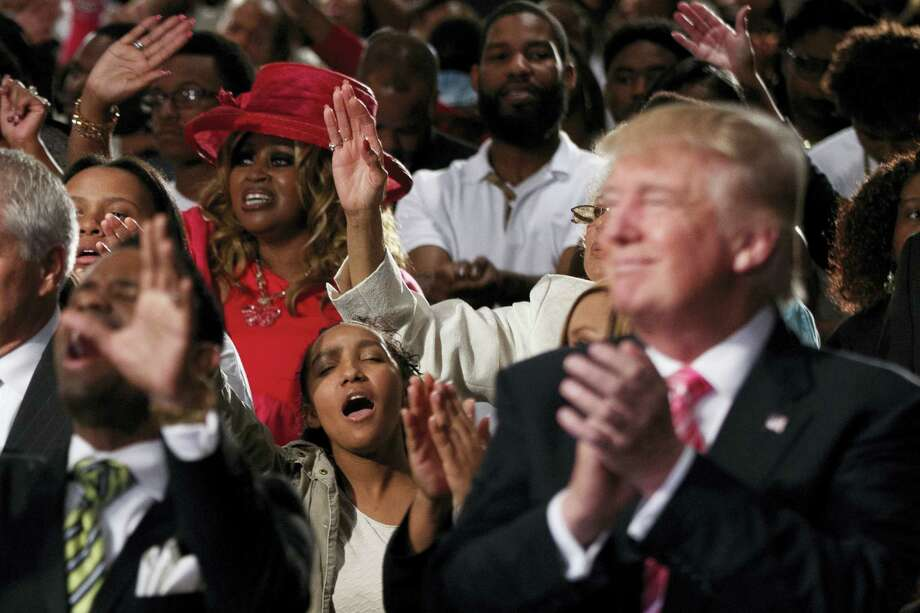 People pray during a church service at Great Faith Ministries with Republican presidential candidate Donald Trump, Saturday, Sept. 3, 2016, in Detroit. Photo: AP Photo — Evan Vucci   / AP