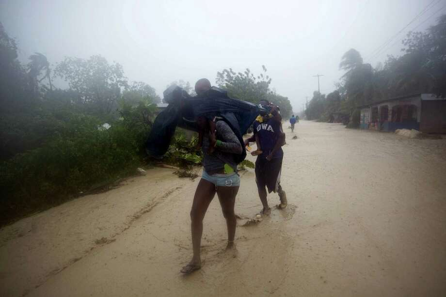 Residents head to higher ground, away from their flooded home in Leogane, Haiti, Tuesday, Oct. 4, 2016. Matthew slammed into Haiti's southwestern tip with howling, 145 mph winds Tuesday, tearing off roofs in the poor and largely rural area, uprooting trees and leaving rivers bloated and choked with debris.  ( AP Photo/Dieu Nalio Chery) Photo: AP / Copyright 2016 The Associated Press. All rights reserved.