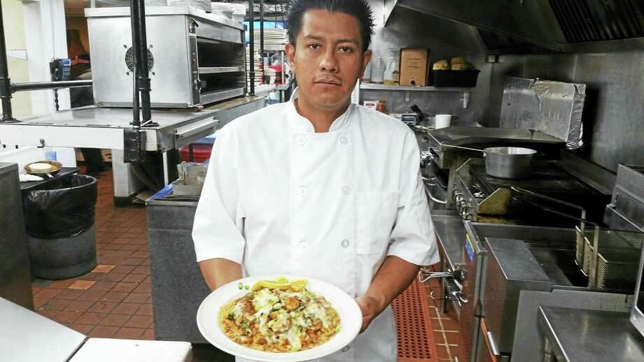 Aunt Chilada's Chef Alfredo Elias shows off his Adobo Chicken, chicken tenders with spinach and mushrooms in a Chipotle sauce with melted cheese. Photo: Shahid Abdul-Karim — New Haven Register