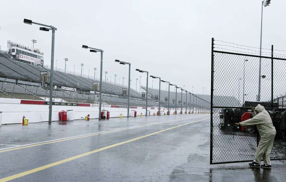 A security guard closes a gate in the garage area in the rain at Darlington Raceway on Friday. Photo: Terry Renna — The Associated Press   / FR60642 AP