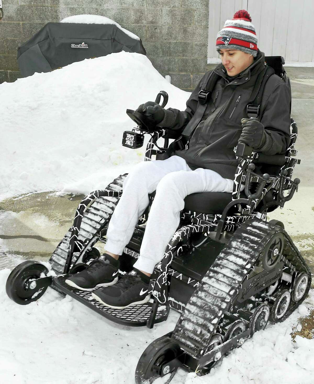Army veteran Sean Pesce, 23, uses an Action Trackstander, a customized and treaded all-terrain vehicle, at his West Haven home earlier this year.