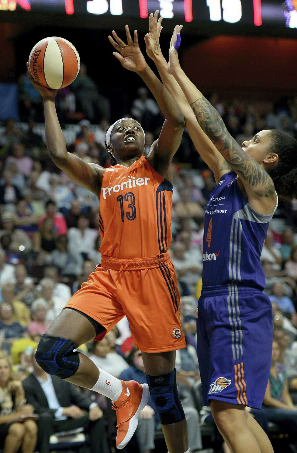 The Sun's Chiney Ogwumike, left, shoots as the Mercury's Candice Dupree defends on Friday.