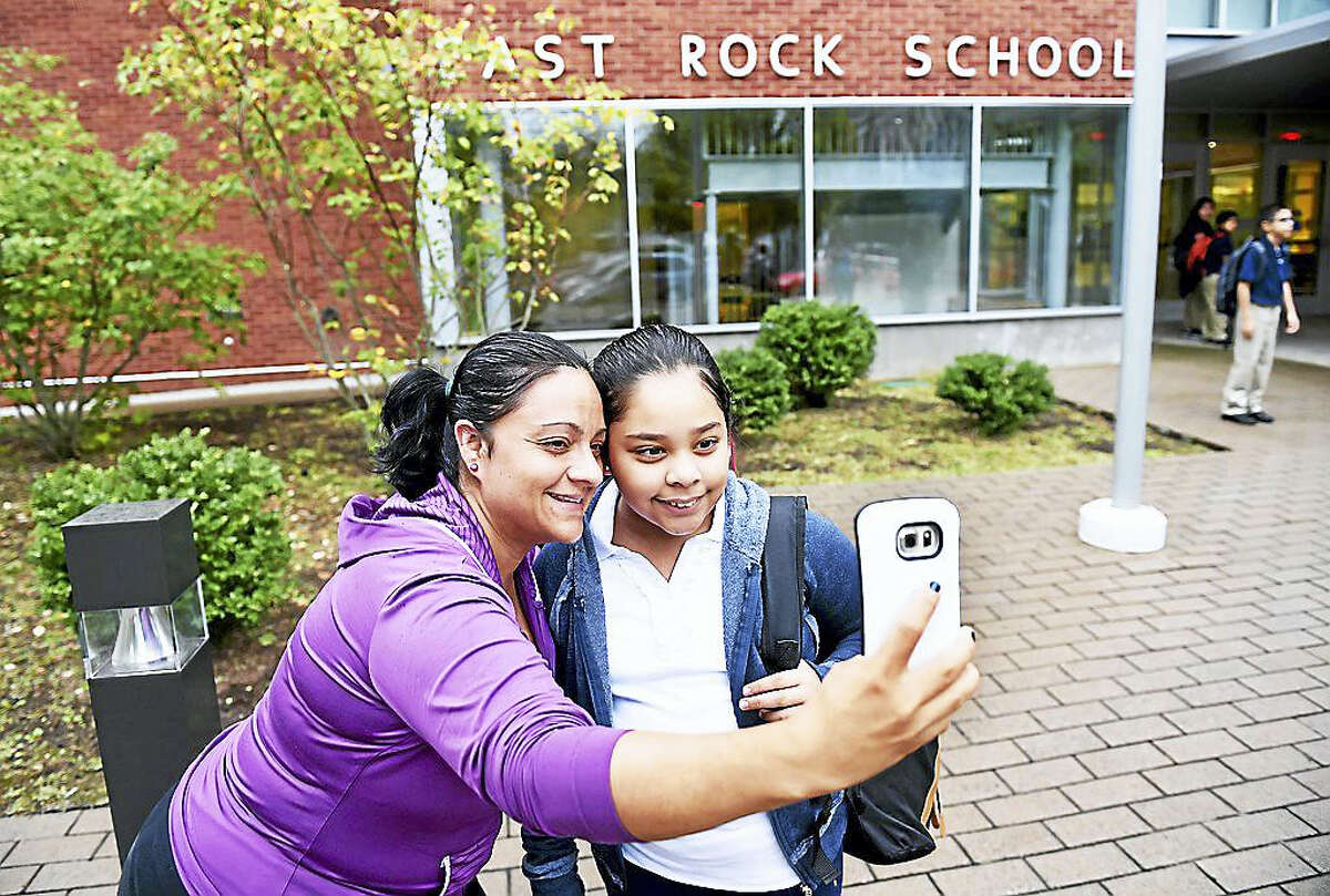 Luciana Clavero, left, takes a selfie with her daughter, Daphne Reyes, 10, in front of East Rock School in New Haven on the first day of school Thursday. Reyes is going into fourth grade.