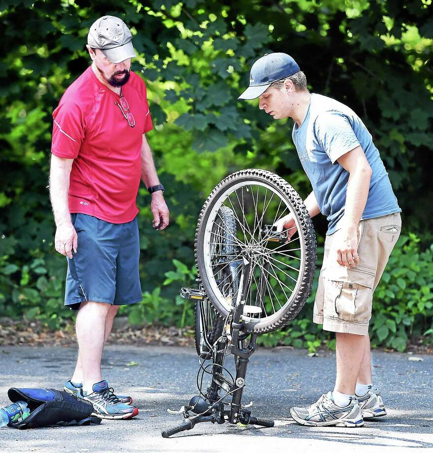Joshua Smith, left, of East Hartford watches his son, Javier, fix a loose chain on his bicycle in a parking lot of the Farmington Canal Greenway in Hamden. Photo: Arnold Gold — New Haven Register File Photo