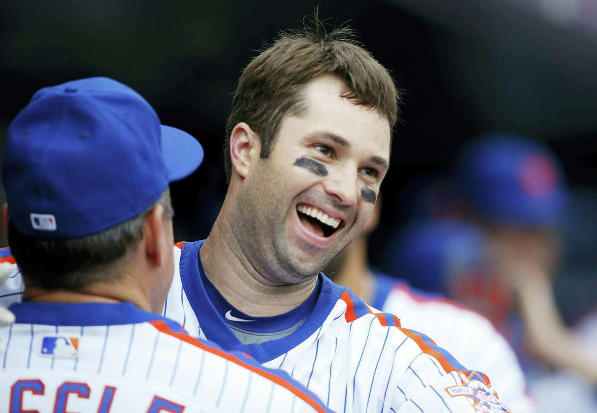 New York Mets second baseman Neil Walker (20) reacts with a coach in the dugout after hitting a go-ahead, three-run home run during the seventh inning of a baseball game against the Colorado Rockies, Sunday, July 31, 2016, in New York. (AP Photo/Kathy Willens)