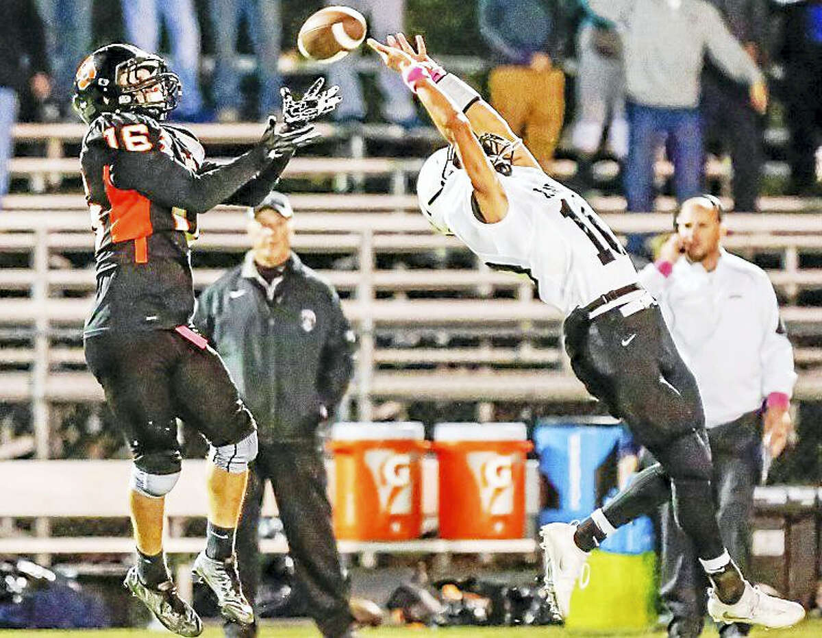 Shelton receiver Anthoony Shiavo (16) catches a pass over the reach of Xaveri Owen Gonzalez(10) to tie the score at 14 during the 2nd quarter during the SCC Tier 1 game Saturday night.