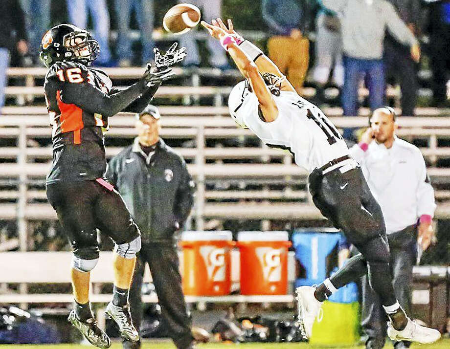 Shelton receiver Anthoony Shiavo (16) catches a pass over the reach of Xaveri Owen Gonzalez(10) to tie the score at 14 during the 2nd quarter during the SCC Tier 1 game Saturday night. Photo: John Vanacore — New Haven Register   / John Vanacore/New Haven Register`