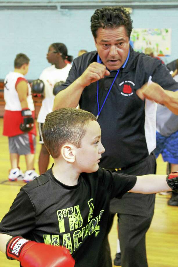 Ansonia Mayor David Cassetti shows a boy how to throw a punch. Photo: Jean Falbo-Sosnovich — New Haven Register