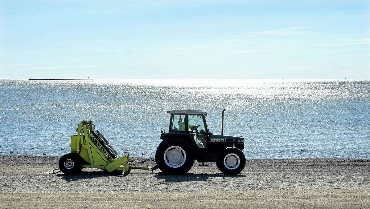 Jim Austin of Milford Public Works rakes the sand near Beach Avenue in Milford Friday morning. The sand at Milford public beaches is raked five days a week from Memorial Day through Labor Day.