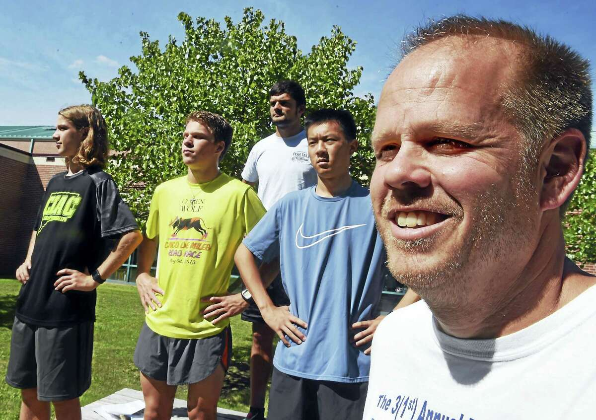 (Peter Hvizdak - New Haven Register) Amity boys cross country coach Jon Faitsch, far right, with assistant coach Dean Bratt, center rear, and his runners, left to right front, junior Andrew Burford, senior Kyle Beaudette, and senior caption Nicholas Yoo.