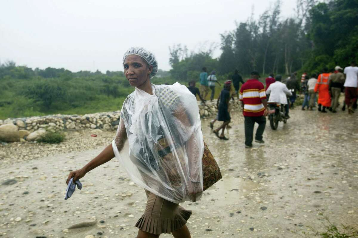A woman protects herself from the rain with a piece of plastic prior the arrival of Hurricane Matthew, in Tabarre, Haiti, Monday, Oct. 3, 2016. The center of Hurricane Matthew is expected to pass near or over southwestern Haiti on Tuesday, but the area is already experiencing rain from the outer bands of the storm. (AP Photo/Dieu Nalio Chery)