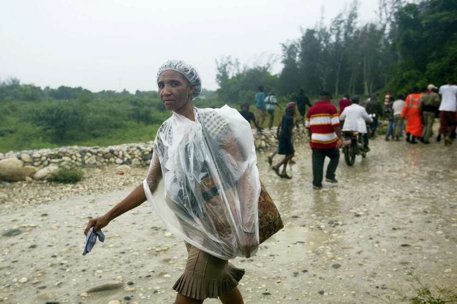 A woman protects herself from the rain with a piece of plastic prior the arrival of Hurricane Matthew, in Tabarre, Haiti, Monday, Oct. 3, 2016. The center of Hurricane Matthew is expected to pass near or over southwestern Haiti on Tuesday, but the area is already experiencing rain from the outer bands of the storm. (AP Photo/Dieu Nalio Chery) Photo: AP / Copyright 2016 The Associated Press. All rights reserved.